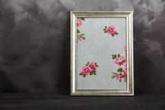 与纹理玫瑰的一张葡萄酒照片框架在破旧的灰色背景 免版税库存照片