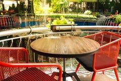 与纹理的空的木桌,与在被弄脏的背景前面的红色椅子 与花、植物和a的一个清淡的街道咖啡馆 库存照片