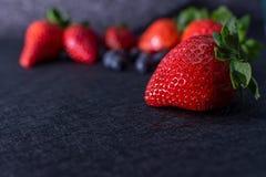 与纹理的黑桌与草莓框架、蓝莓和红色果子 免版税库存照片