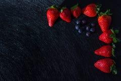与纹理的黑桌与草莓框架、蓝莓和红色果子 免版税图库摄影