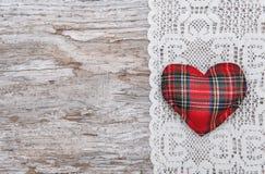 与纺织品心脏的华伦泰卡片在鞋带和老木头 库存图片