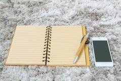 与线的特写镜头棕色笔记本在页、棕色笔和巧妙的电话在灰色织品capet构造了背景在顶视图在工作 免版税库存照片