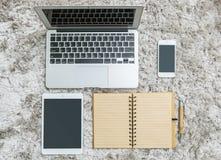 与线的特写镜头棕色笔记本在页、笔、计算机笔记本、片剂和巧妙的电话在灰色织品capet构造了backgro 免版税库存照片