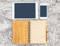 与线的特写镜头棕色笔记本在页,棕色笔、片剂和巧妙的电话在灰色织品capet被构造的背景在上面竞争 免版税库存照片