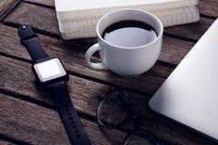 与组织者、膝上型计算机、眼镜和巧妙的手表的无奶咖啡在木桌上 库存照片
