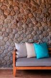 与织品位子和枕头的长木凳投入了对石墙 库存照片