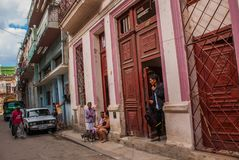 与经典老汽车和传统五颜六色的大厦的街道场面在街市哈瓦那 古巴 库存照片