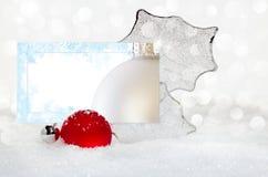 与结霜的看板卡的银色&红色圣诞节装饰品 免版税库存图片