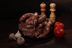 与绞肉机的芬芳自创德国香肠圆白菜链接在木桌上的一块板材放置 香肠允许与keto饮食 免版税库存照片