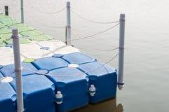与绳索篱芭的塑料浮船 免版税库存图片