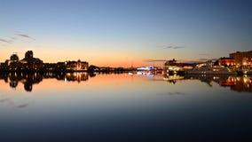 与维多利亚市和日落光芒明亮的平衡的光的地平线  光形成在海湾的水的一个镜象 库存照片