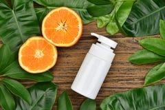 与维生素C萃取物,有新橙色切片的化妆瓶容器的化妆用品skincare 免版税库存照片