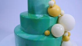 与绿松石镜子釉的时髦的奶油甜点蛋糕 与绿松石用巧克力球装饰的镜子釉的蛋糕 免版税库存图片