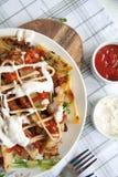 与绿色、大蒜和调味汁的被烘烤的土豆在一块白色板材 免版税库存照片