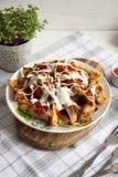 与绿色、大蒜和调味汁的被烘烤的土豆在一块白色板材 免版税图库摄影