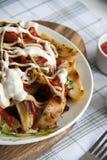 与绿色、大蒜和调味汁的被烘烤的土豆在一块白色板材 库存图片