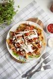 与绿色、大蒜和调味汁的被烘烤的土豆在一块白色板材 库存照片