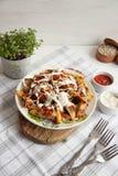 与绿色、大蒜和调味汁的被烘烤的土豆在一块白色板材 免版税库存图片
