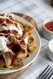 与绿色、大蒜和调味汁的被烘烤的土豆在一块白色板材 图库摄影