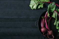 与绿色上面的甜菜在深黑色木背景,在背景厨房用桌顶视图的新鲜的红色甜菜根的圆的金属平底锅 免版税图库摄影