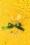 与绿色丝带,以星的形式金黄五彩纸屑的香宾玻璃在黄色背景舱内甲板被放置的顶视图 创造性 库存图片