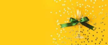 与绿色丝带,以星的形式金黄五彩纸屑的香宾玻璃在黄色背景舱内甲板被放置的顶视图 创造性 库存照片