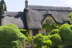 与绿色修剪的花园庭院的田园诗老英国村庄 免版税库存图片