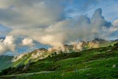 与绿色倾斜的美好的山风景和雪和云彩 免版税库存照片