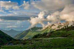 与绿色倾斜的美好的山风景和雪和云彩 图库摄影