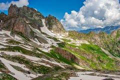 与绿色倾斜的美好的山风景和雪和云彩 库存照片
