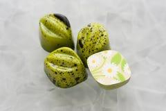 与绿色光亮的涂层的手工制造巧克力糖与与daisieson的黑下落白色表面无光泽的玻璃背景 库存照片