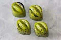 与绿色光亮的涂层的手工制造巧克力糖与在白色表面无光泽的玻璃背景的黑下落 库存图片