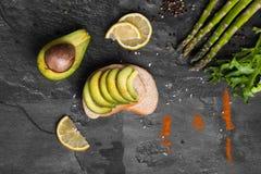 与绿色切片的一个三明治鲕梨洒与调味料,芦笋,沙拉在灰色背景离开 免版税库存图片