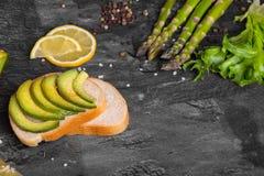 与绿色切片的一个三明治鲕梨洒与调味料,芦笋,沙拉在灰色背景离开 库存照片