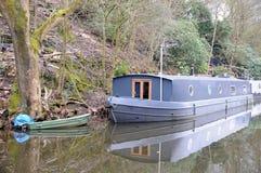 与绿色划艇的灰色驳船居住船在运河停泊了 免版税库存图片