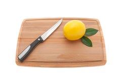 与绿色叶子和一把刀子的黄色柠檬在一个木厨房c 免版税库存照片