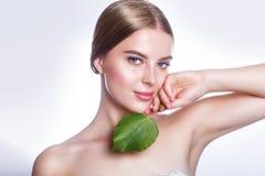 与绿色叶子概念的美丽的妇女面孔画象护肤或有机化妆用品的 工作室纵向 免版税库存照片