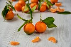 与绿色叶子的两个新鲜的蜜桔 在灰色木板的被剥皮的橘子和蜜桔橙色切片 柑橘 免版税库存图片