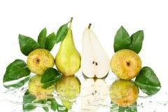 与绿色叶子的会议梨和在白色背景被隔绝的关闭的一个被削减的梨一半 库存图片