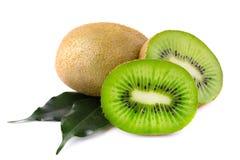 与绿色叶子的成熟水多的猕猴桃切片,被隔绝 免版税库存图片