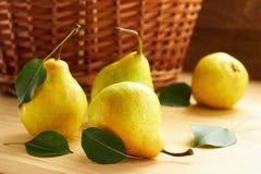 与绿色叶子的新鲜的梨在木背景的wattled篮子前面 免版税库存照片