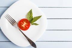 与绿色叶子的自然有机在白色板材的蕃茄和叉子饮食早餐或晚餐的 与拷贝空间的顶视图 健康 免版税库存图片