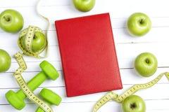 与绿色哑铃的红色与测量的磁带的笔记薄和苹果 库存照片