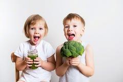 与绿色圆滑的人和硬花甘蓝的两个俏丽的乐趣孩子在白色 免版税库存照片