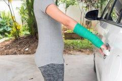 与绿色在手边被熔铸的和胳膊的伤害妇女佩带的体育商品 免版税库存照片