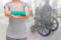 与绿色在手边被熔铸的和胳膊的伤害妇女佩带的sportsware 图库摄影