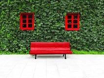 与绿色垂直的庭院的门面和在一个能承受的大厦的红色窗口 免版税库存图片