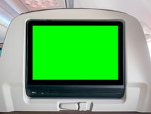 与绿色屏幕,有绿色屏幕的Seatback屏幕的飞行中娱乐在飞机 免版税库存图片