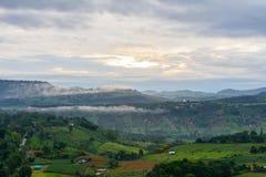 与绿色山的乡下场面在日出 免版税库存图片
