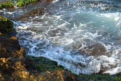与绿色岩石岸和泡沫ne的美好的海波浪背景 图库摄影